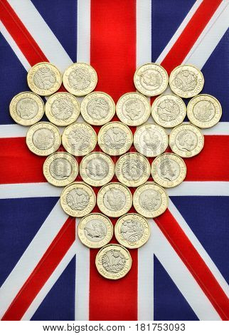 New British pound coins in the shape of a heart on a Union Jack flag. This one pound coin was introduced in March 2017.