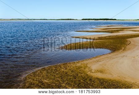 Orange crests of the sandbanks stretch out deep in the blue water of the river