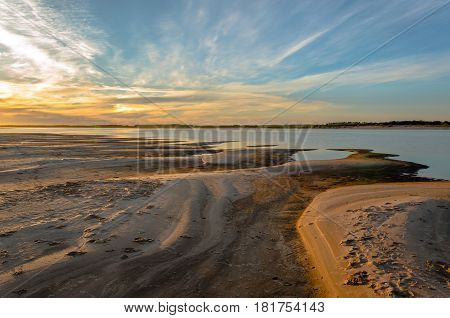 Sunset blue sky, a wide blue river, a large sandy beach