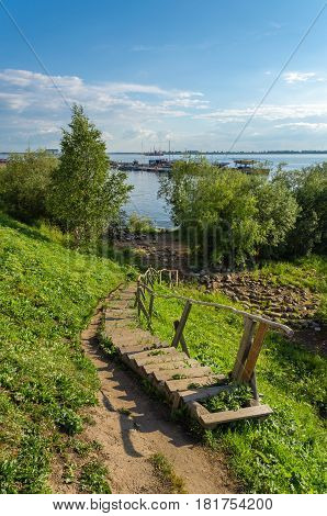 Wooden stairs with handrail lead down to the wooded banks of the river