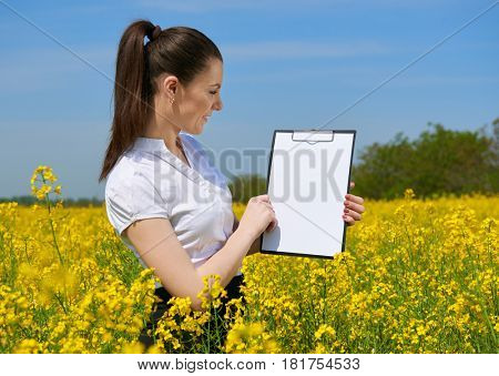 Business woman in flower field outdoor look on clipboard. Young girl in yellow rapeseed field. Beautiful spring landscape, bright sunny day