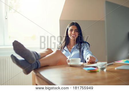 Happy Female Adult In Socks With Feet On Desk