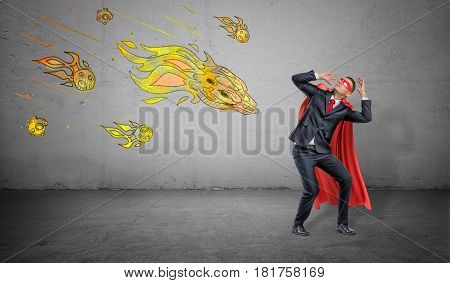 A scared businessman in a superhero cape cowering under an attack of yellow paper comets on concrete background. Business and competitors. Crisis management. Protective strategy.
