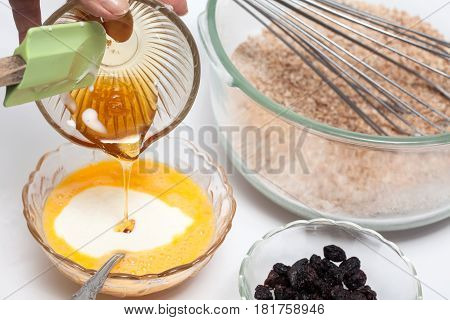 Wheat bran muffins preparation : Adding honey to the mix to prepare integral wheat bran muffins
