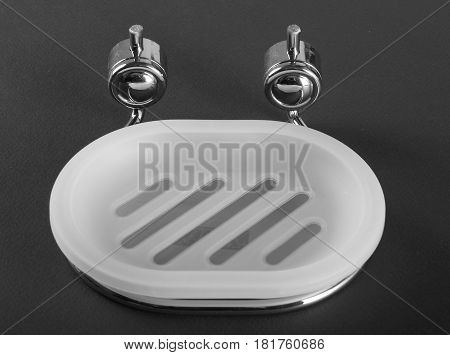Empty white plastic soap-dish with metal holder on gray background