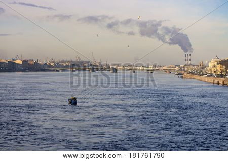 Fishing boat at sunrise on the Neva river on the background of the Annunciation bridge and of Smoking pipes companies
