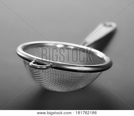 Close up of metallic strainer with plastic handle a modern kitchen utensil