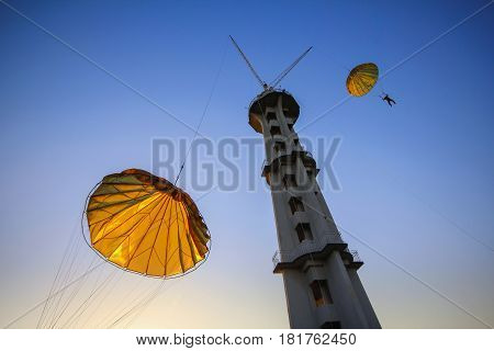 Jumping from a parachute tower. Blue sky and yellow parachutes.