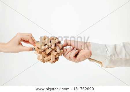 The wooden puzzle in male and female hands isolated on white background