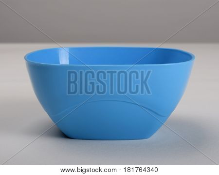 Blue plastic deep dish on the table front view