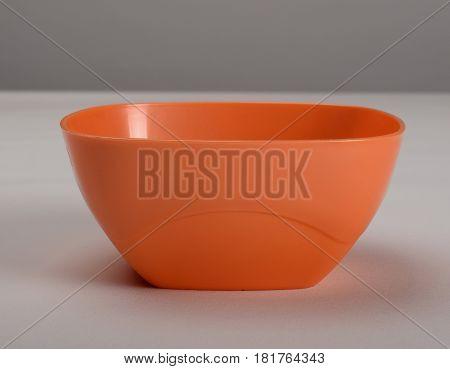 Orange plastic deep dish on the table