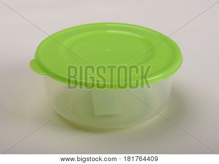 Round plastic container with green lid on white background