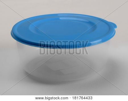 Round plastic container with blue lid on white background