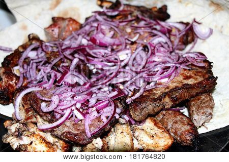 The meat on the grill. Meat covered with fried red onion. Simply cook and serve. It is fragrant and exudes a pleasant smell of roasted meat.