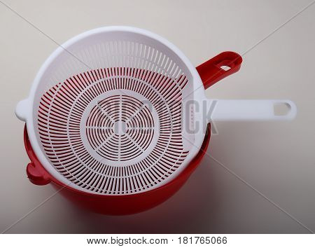 White plastic colander in red bowl isolated on white background