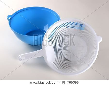 White plastic colander to blue bowl isolated on white background