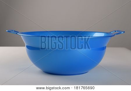 Blue deep plastic bowl with two handles
