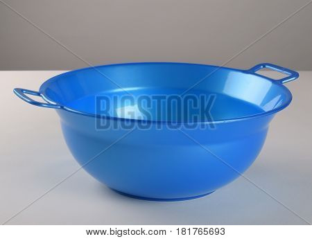 Blue deep plastic bowl with handles in the kitchen