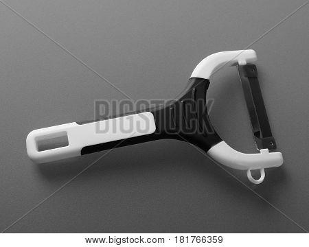 Potato peeler with handle on gray background
