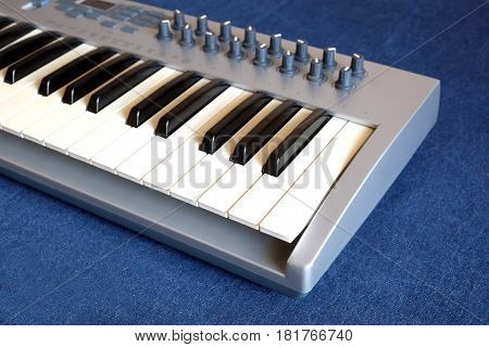 Electronic synthesizer keyboard with many control knobs on denim background side view closeup