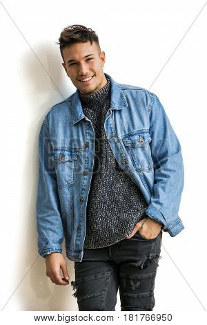 Handsome white asian young man wearing blue denim jacket smiling, standing on light background against wall in studio shot