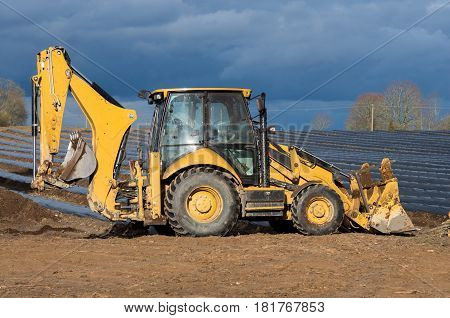 Small Yellow Excavator Stay At The Beds After Work.