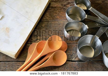 Measuring Cups, Wooden Mixing Spoons, and Old Cookbook.