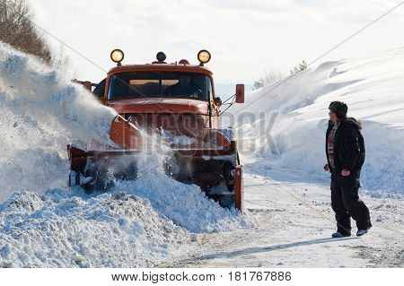 Chelyabinsk Region, Russia - February 25, 2008: Traffic jam at interurban road caused by heavy snowstorm. Machinery with snowplough cleaning road by removing snow from intercity highway after winter blizzard