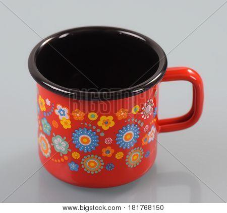 Enamel mug with handle on isolated white background