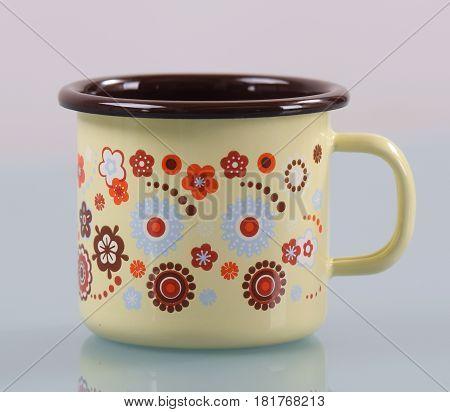 Empty enamel mug with handle, isolated on white background