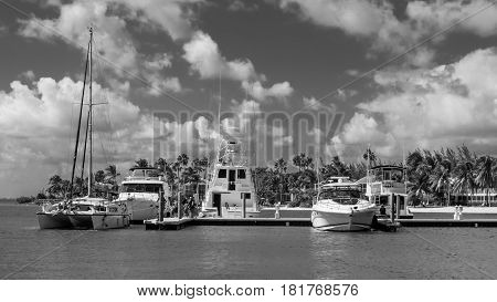 Marina and boats on the Caribbean sea with a seafront at Kaibo in Cayman Islands (b&w)