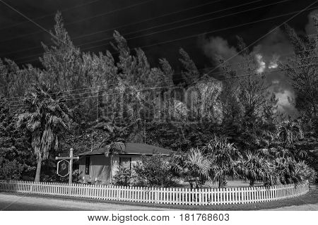Building by the roadside in a tropical garden surrounded by a wooden white fence in Cayman islands (b&w)