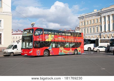 SAINT-PETERSBURG, RUSSIA, APRIL 15, 2017: Hop-On Hop-Off. People in The City Tour Bus rides from the excursion bus parking near The Palace Square and The State Hermitage Building