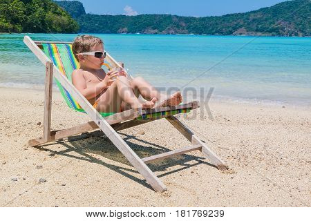 A little boy in chaise longue against background of the sea drinking juice from straw