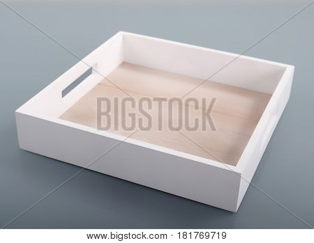 One white wooden tray on gray background