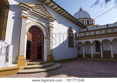 Arched side entrance with wood doors and decorated dome of Iglesia de Guadalupe Catholic church in San Cristobal de las Casas Chiapas Mexico