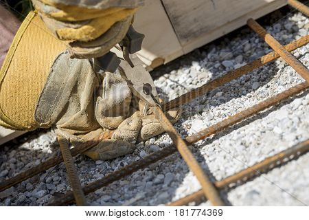 Worker tying steel reinforcing rods with string to position them over a stone gravel base.