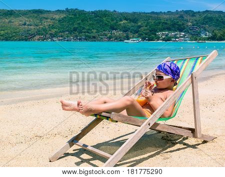 Little boy in chaise longue against sea drinking juice