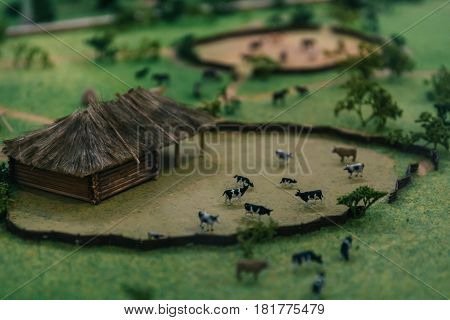 Miniature layout or model or maquette landscape of village with small house and animals. Selective focus