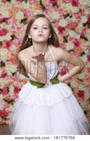 Blow kiss, young caucasian blonde little girl on the background of flowers wall studio