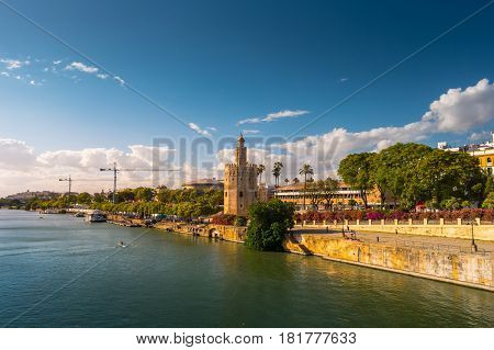 View of Golden Tower, Torre del Oro, of Seville, Andalusia, Spain over river Guadalquivir at sunset. Clouds over historic buildings.