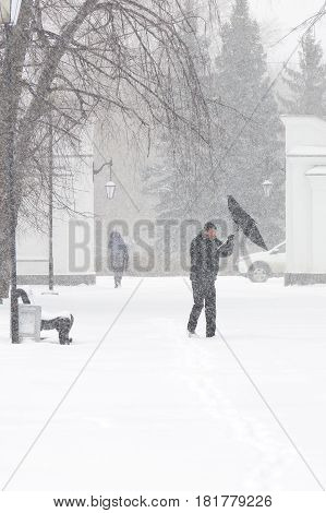 Bad weather in a city: a heavy snowfall and blizzard in winter. Unidentified male pedestrian hiding from the snow under umbrella. Heavy gust of wind tears the umbrella out of his hands, vertical
