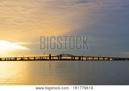 Beautiful golden violet sunrise over calm tranquil lake long bridge at horizon