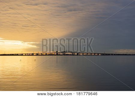 Peaceful blue and golden colorful sunrise over Skyway bridge and calm lake waters dramatic sky and clouds