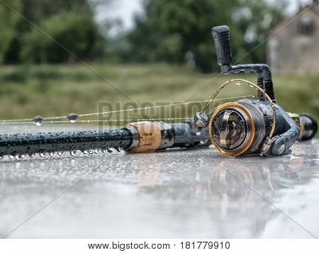 The fishing rod with the reel lies in the rain. Drops of water hang from the fishing rod.