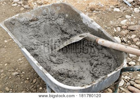 Wheelbarrow full of concrete and shovel for building