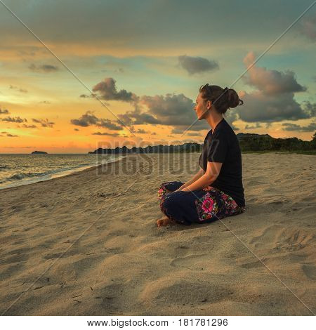 Woman sitting on beach sand doing yoga meditating and relaxing at sunset time
