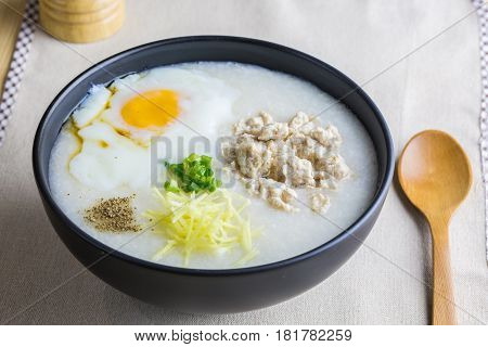 Close up to rice porridge is topping with ginger spring onion pepper chicken and onsen egg Breakfast set on table spoon pepper grinder. breakfast in Asia call