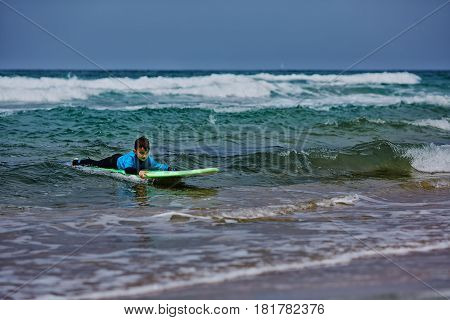 Boy surfer surfing waves on the beach enjoying fun