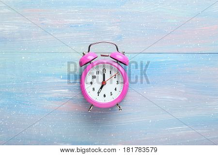 Pink Alarm Clock On Blue Wooden Table
